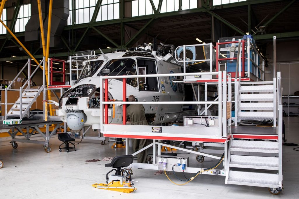 Military helicopter in workshop for maintenance.