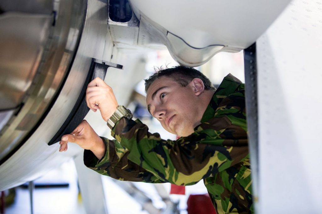 Military men checking the engine of aeroplane with 3D printed jigs.