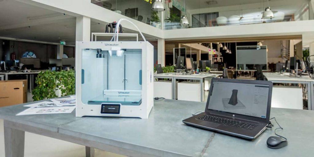 Ultimaker S5 3D štampač i laptop na kojem je pokrenut Ultimaerk CURA softver za pripremu za štampu u otvorenom kancelarisjkom prostoru.