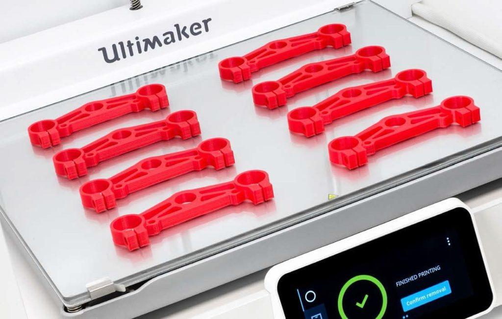 Krupan kadar radne površine 3D štampača Ultimaker S5 sa završenim crvenim delovima.