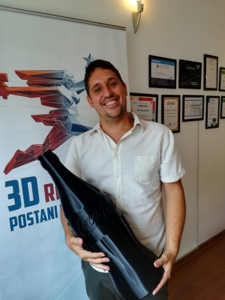 Čovek u kancelariji kompanije 3D Republika sa velikom flašom u rukama izrađenoj na 3D štampaču Raise3D Pro 2 Plus